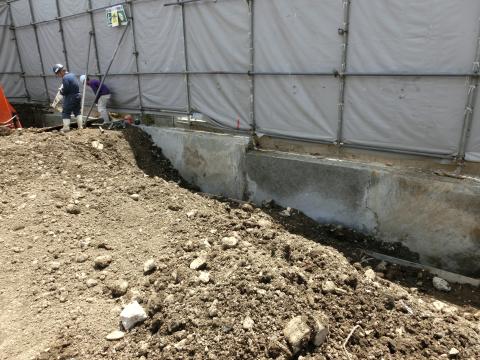 写真:コンクリートの土留めを新設しながら進める解体作業の様子