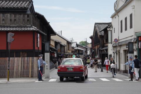 写真:石畳と町家の風情でたくさんの観光客が歩いているのにクルマが通れる花見小路(土日ぐらいは歩行者専用にできないものか?)