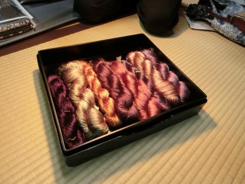 写真:白熱電球に照らされると華やかな色になる染め糸