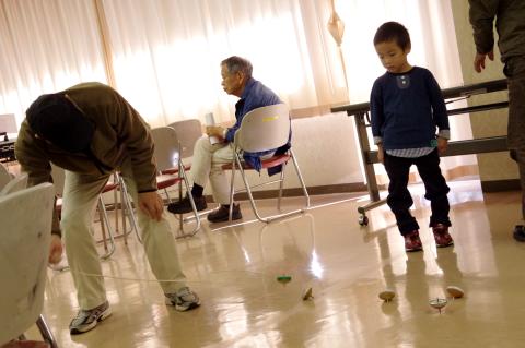 写真:コマ回し。お年寄りは手慣れたものです。