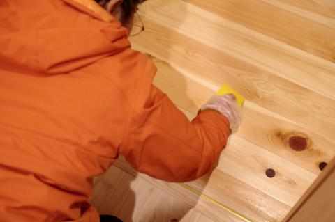 写真:桧無垢材の床にオイル塗料を塗る作業の様子